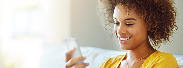 Young woman checks her UW Credit Union account on a mobile device.