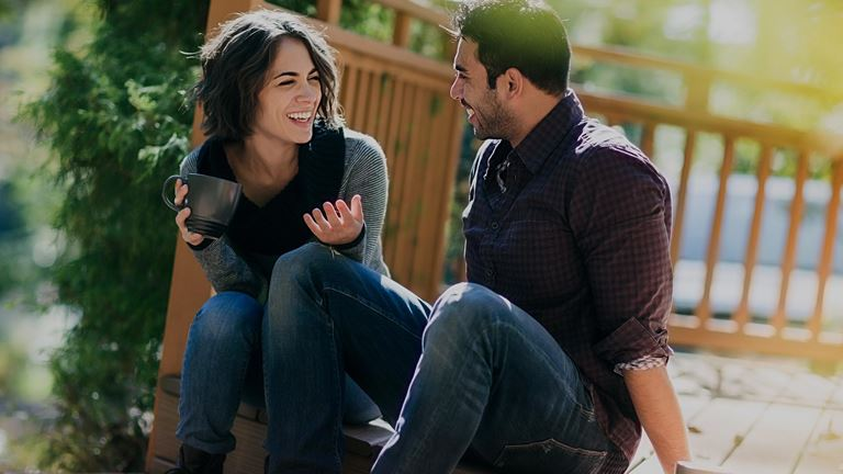 Couple laughs together on a deck.
